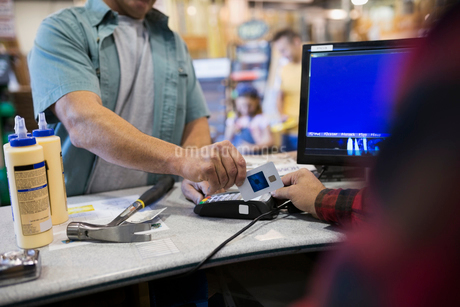 Man paying using credit card reader at home improvement storeの写真素材 [FYI02308990]