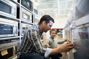 Father and son measuring oven in appliance storeの写真素材 [FYI02309058]