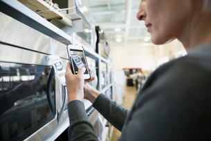 Woman with camera phone photographing microwave price tag in appliance storeの写真素材 [FYI02309062]