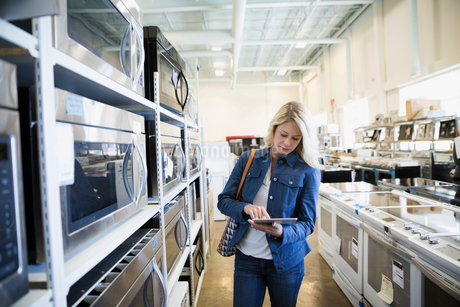 Woman with digital tablet shopping for microwave in appliance storeの写真素材 [FYI02309067]