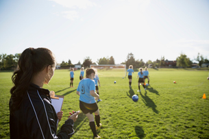Coach watching and timing middle school girl soccer team running drills at practice on sunny fieldの写真素材 [FYI02309093]