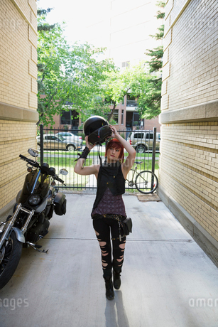Cool woman with ripped jeans removing motorcycle helmet in urban alleyの写真素材 [FYI02309108]