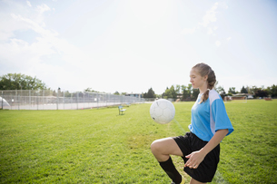 Middle school girl soccer player bouncing ball on knee on sunny fieldの写真素材 [FYI02309132]