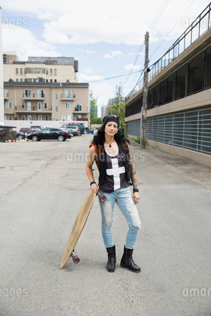Portrait cool mature woman with skateboard in urban alleyの写真素材 [FYI02309140]