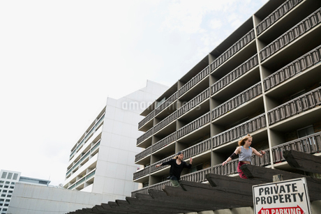 Young man free running below urban apartment buildingsの写真素材 [FYI02309147]