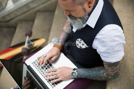 Hipster with tattoos typing on laptop on stairの写真素材 [FYI02309208]