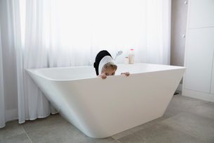 Portrait shy boy in killer whale costume hiding in bathtubの写真素材 [FYI02309214]