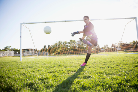 Middle school girl soccer goalie kicking the ball on sunny fieldの写真素材 [FYI02309219]