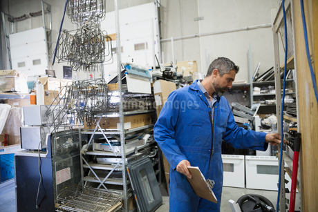 Worker in coveralls with clipboard in appliance repair workshopの写真素材 [FYI02309309]