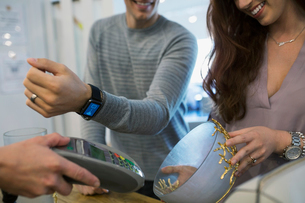 Man paying using smart watch contactless payment at home furnishings storeの写真素材 [FYI02309337]