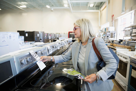 Senior woman with sale ad checking price tag on stove in appliance storeの写真素材 [FYI02309394]