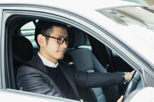 車を運転する笑顔の30代男性の写真素材 [FYI02309418]