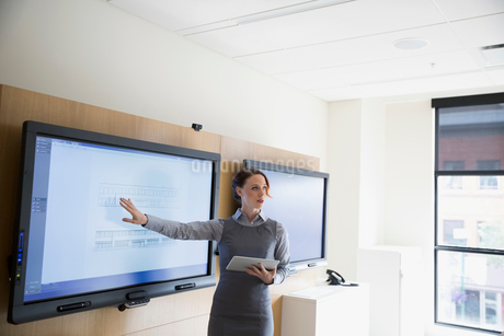 Businesswoman with digital tablet leading meeting at television in conference roomの写真素材 [FYI02309431]