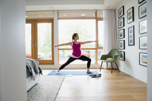 Pregnant woman practicing warrior 2 yoga pose in bedroomの写真素材 [FYI02309459]
