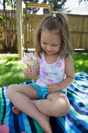 Girl eating melting messy ice cream cone on blanket in backyardの写真素材 [FYI02309495]