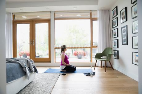 Pregnant woman practicing yoga on bedroom floorの写真素材 [FYI02309526]