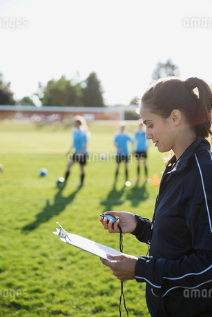 Coach with clipboard timing middle school girl soccer team running drills at practice on sunny fieldの写真素材 [FYI02309541]