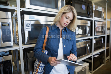 Woman with digital tablet shopping for microwave in appliance storeの写真素材 [FYI02309584]