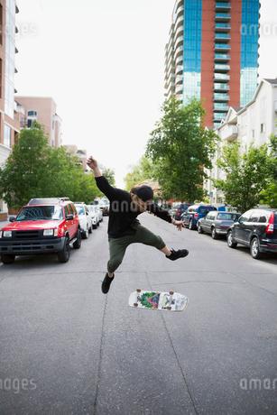Cool young man flipping skateboard in urban streetの写真素材 [FYI02309600]