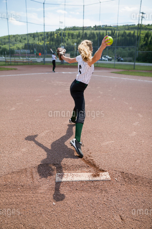 Middle school girl softball pitcher pitching ball on baseball diamondの写真素材 [FYI02309616]