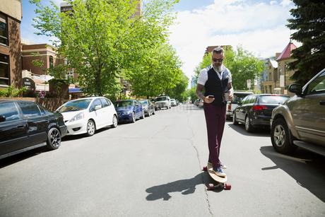 Cool hipster man with coffee riding skateboard and texting on sunny streetの写真素材 [FYI02309631]