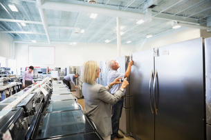 Senior woman with camera phone photographing refrigerator in appliance storeの写真素材 [FYI02309632]