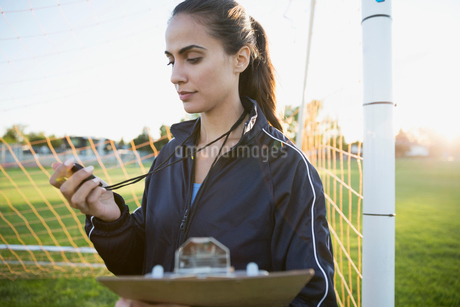 Soccer coach with stopwatch and clipboard at goal netの写真素材 [FYI02309653]