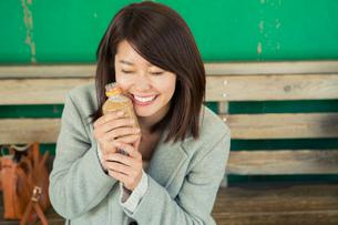 温かいドリンクに癒される笑顔の20代女性の写真素材 [FYI02309680]