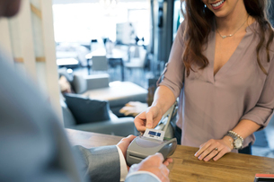 Woman paying using credit card reader in home furnishings storeの写真素材 [FYI02309688]