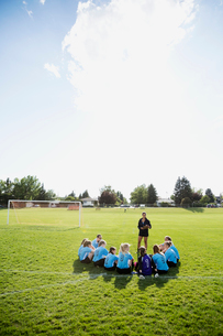 Coach talking to middle school girl soccer team on sunny fieldの写真素材 [FYI02309702]