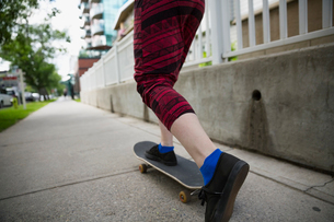 Young woman skateboarding on urban sidewalkの写真素材 [FYI02309725]
