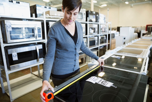 Woman measuring stove in appliance storeの写真素材 [FYI02309767]