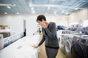 Woman talking on cell phone shopping for clothes washer in appliance storeの写真素材 [FYI02309779]