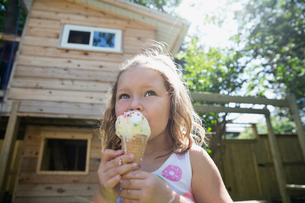 Girl eating melting messy ice cream cone in sunny backyardの写真素材 [FYI02309780]