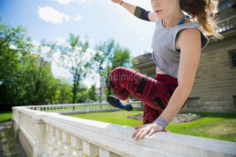 Young woman doing parkour jumping over railingの写真素材 [FYI02309820]