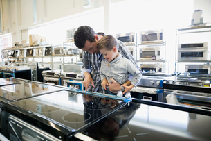 Father and son shopping for stove in appliance storeの写真素材 [FYI02309846]