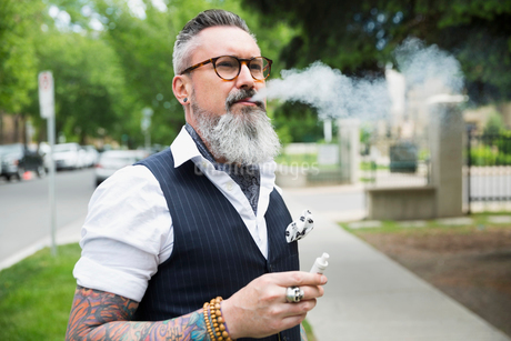 Cool hipster with gray beard and tattoos smoking cigarette on urban sidewalkの写真素材 [FYI02309865]