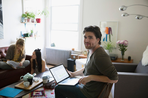 Portrait confident young activist with laptop meeting planning in living roomの写真素材 [FYI02309884]