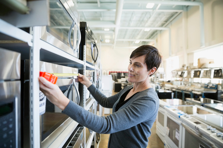 Woman measuring microwave in appliance storeの写真素材 [FYI02309916]