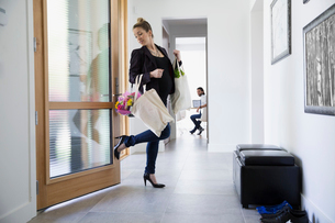 Smiling businesswoman returning home with groceries and flowers closing door with foot in foyerの写真素材 [FYI02309920]