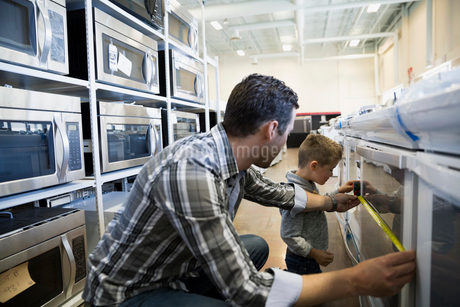 Father and son measuring oven in appliance storeの写真素材 [FYI02309927]