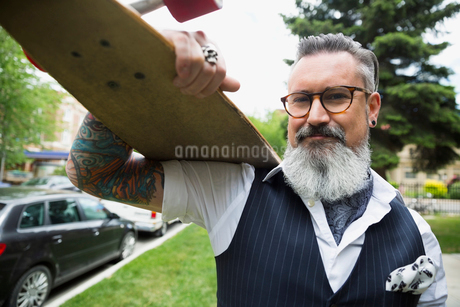 Portrait hipster with tattoos and gray beard holding skateboard in parkの写真素材 [FYI02309937]