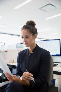 Businesswoman reviewing paperwork in officeの写真素材 [FYI02309946]