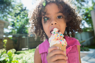 Close up portrait girl eating ice cream cone with sprinkles in sunny backyardの写真素材 [FYI02309988]