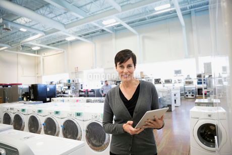 Portrait confident saleswoman with digital tablet in appliance storeの写真素材 [FYI02310002]