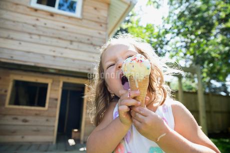 Girl eating melting messy ice cream cone in sunny backyardの写真素材 [FYI02310033]