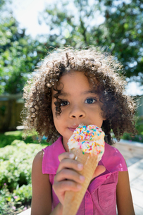Close up portrait girl eating ice cream cone with sprinkles in sunny backyardの写真素材 [FYI02310060]