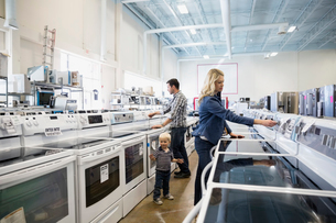 Young family shopping for stoves in appliance storeの写真素材 [FYI02310126]