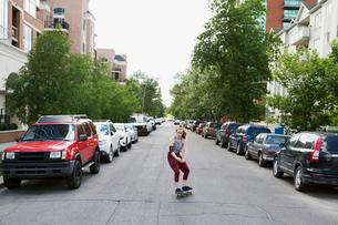 Cool young woman skateboarding in urban streetの写真素材 [FYI02310151]