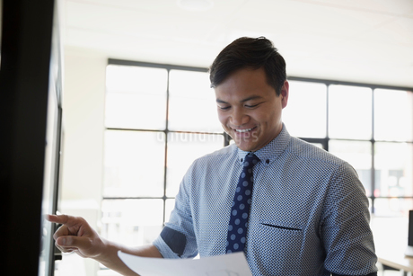 Smiling businessman with paperwork using touch screen television in conference roomの写真素材 [FYI02310155]